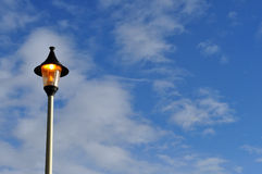 Orange lit street light Blue skies and clouds Royalty Free Stock Image