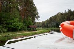 Orange livboj på en skeppsegling längs floden nära skogen Fotografering för Bildbyråer