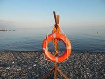 Orange livboj på ett Pebble Beach på Blacket Sea Arkivbild