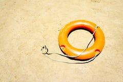 Orange livboj på stranden Royaltyfri Bild
