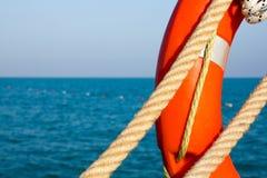 Orange livpreserver och maritimt rep två på bakgrunden av det blå havet och himmel close upp Livboj på bakgrunden av havet royaltyfri fotografi