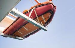 Orange livräddningsbåt som hänger på skeppet på havet Royaltyfria Foton