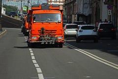Orange LKW, der entlang die Straße fährt Stockbild