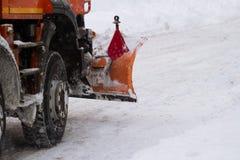 Orange LKW mit dem Pflug, der hinunter Schnee auf einer Stadtstraße fährt Stockbilder
