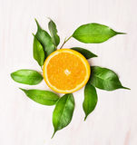 Orange lobule with green leaves on white wooden table. Top view Royalty Free Stock Images