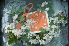 Orange long metal scissors lying on the edge of the dial square orange watch among abundance of spring flowers of apple and foliag. Orange long metal scissors Royalty Free Stock Photos
