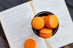 Orange macaroon upon open diary with notes. Orange colored macaroon upon open diary with notes Stock Photos