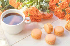 Orange macaroons, cup of coffee and fresh roses Stock Image