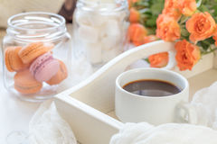 Orange macaroons, cup of coffee and fresh roses Royalty Free Stock Photography