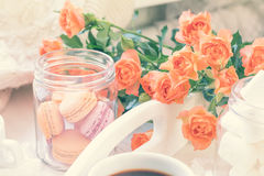 Orange macaroons, cup of coffee and fresh roses Stock Photo