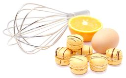 Orange Macaroon. A display of orange macroon accompanied with egg , oranges and wire whisk on white back ground Stock Photo