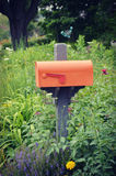 Orange Mailbox. An orange colored United States post office mailbox with a red flag surrounded by beautiful flower gardens Royalty Free Stock Image