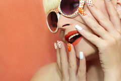 Orange makeup and nail design with white dots. Royalty Free Stock Photography
