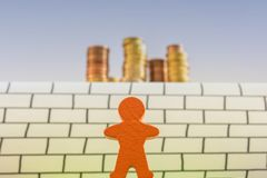 Wooden figures stand in front of an insurmountable wall with a big money tower behind royalty free stock photos