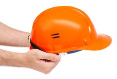 Orange man`s helmet in male hand. On a white background isolation Stock Image
