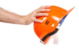 Orange man`s helmet in man`s hand. On a white background isolation Royalty Free Stock Photography