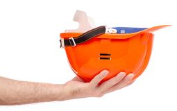 Orange man`s helmet in man`s hand. On a white background isolation Royalty Free Stock Photo