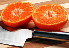 Orange mandarin. Cutted in half with knife on a wood cutting board Stock Image