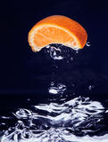 Orange (mandarin) falling in blue water Stock Photos