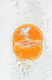 Orange (mandarin) falling in clear water Stock Photo