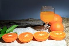 Orange Mandarinen- oder Tangerinefrüchte, mit grünen Blättern und Orangensäften im Glas auf Hintergrund des hölzernen Brettes Lizenzfreie Stockbilder