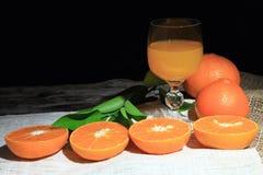 Orange Mandarinen- oder Tangerinefrüchte, mit grünen Blättern und Orangensäften im Glas auf Hintergrund des hölzernen Brettes Stockfotografie