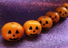 Orange mandariner i form av en pumpa målade i form av symboler av allhelgonaaftonen på den briljanta purpurfärgade bakgrunden Arkivbild