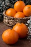 Orange mandarines. In basket on wooden table Stock Image