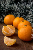 Orange mandarines. On wooden table, one of which is peeled Stock Photos