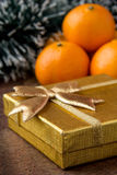 Orange mandarines and gold gift. On wooden table Stock Images