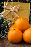 Orange mandarines and gold gift. On wooden table Stock Photos