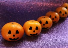 Orange mandarins in the form of a pumpkin painted in the form of icons of Halloween on the brilliant purple background. Closeup Stock Photography