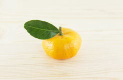 Orange mandarins with green leaf. Isolated on wood background Royalty Free Stock Images