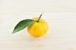 Orange mandarins with green leaf. Isolated on wood background Stock Photos
