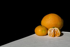 Orange and mandarins on white table with black background Royalty Free Stock Photography