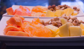 Orange, mango, papaya pieces and nuts on white plates. Stock Image