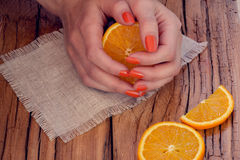 Orange manicure and oranges Stock Photo