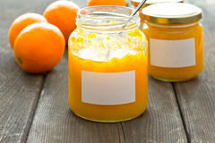 Orange marmalade jars labels oranges. Two jam jars of home made orange marmalade with white labels, one open with a spoon inside, on an old dark wood table Stock Photo