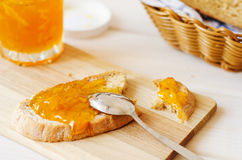 Orange marmalade spread spoon on homemade fresh bread Royalty Free Stock Image