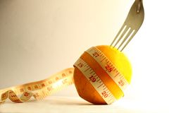 Orange with measurement tape and fork Stock Photos