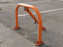 Orange mechanical parking barrier with a lock on the gray aswhite stripephalt royalty free stock photography