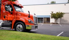 Orange rig middle class semi truck tractor on warehouse parking Stock Photos