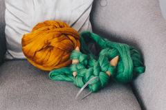 Orange merino wool ball with green knitted blanket Royalty Free Stock Image