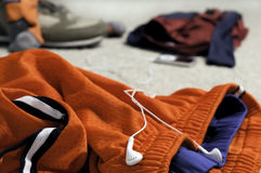 Orange mesh shorts in a messy room. This is a pair of orange mesh lacrosse shorts with a pair of white headphones in a messy room with other sports/exercise Royalty Free Stock Photos