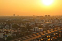 Orange metropolis. Blurred city and express way under dust in the air under orange sky with big yellow sun Royalty Free Stock Image