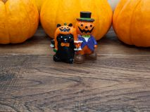 Orange miniature ceramic pumpkin guy with black cat with three orange pumpkins on the background. Over dark wooden surface with copy space used in Halloween stock image
