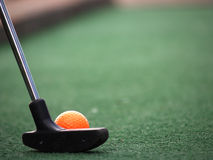 Orange Miniature Golf ball. A miniature golf ball sitting in front of the golf club Royalty Free Stock Images