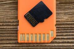 Orange minnesSD-kort, gammal wood bakgrund Arkivfoton