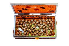 Orange Miror Box filled with golden beads Royalty Free Stock Images