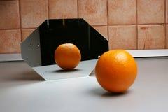 Orange in the mirror Stock Photos